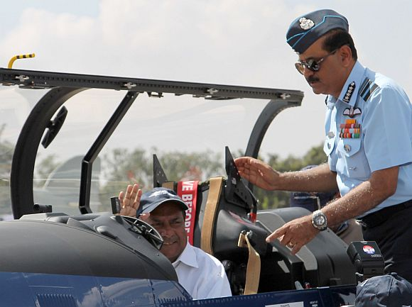 Defence Minister A K Antony in the cockpit of the Pilatus Trainer Aircraft at Aero India 2013. Alongside: Air Chief Marshal Norman Anil Kumar Browne.
