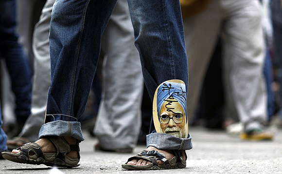 A supporter of activist Anna Hazare wears a cut-out of Prime Minister Manmohan Singh during a protest against corruption
