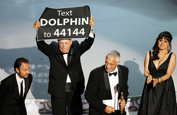 Director Louie Psihoyos accepts an award with producer Fisher Stevens, producer Paula DuPre Pesman, as cast member Richard O'Barry holds up a sign after 'The Cove' won best documentary feature during the 82nd Academy Awards in Hollywood March 7, 2010