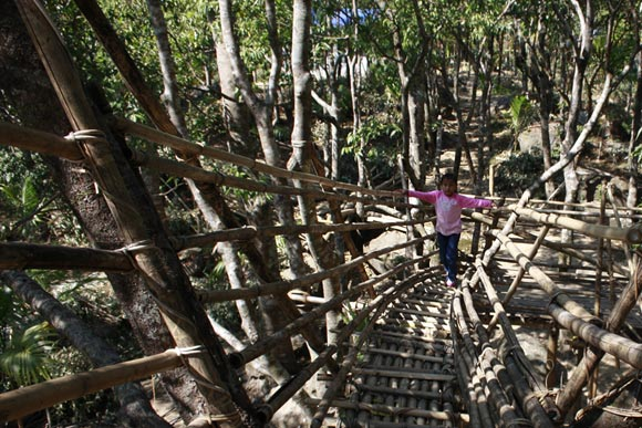 A bamboo staircase leads to a vantage point with a view of Bangladesh