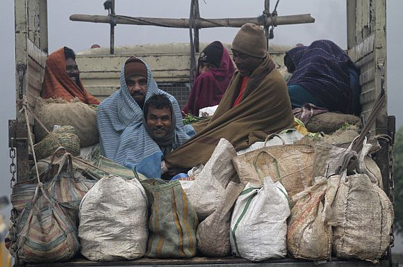 Vendors covered in blankets sit in the back of a supply truck after buying vegetables from a market on a cold winter morning