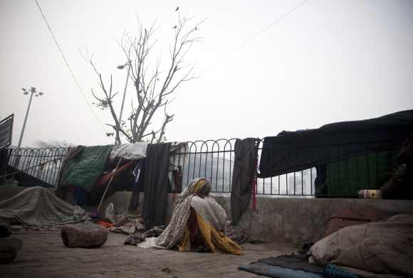 A homeless woman sits on a chilly morning beside a main road in New Delhi