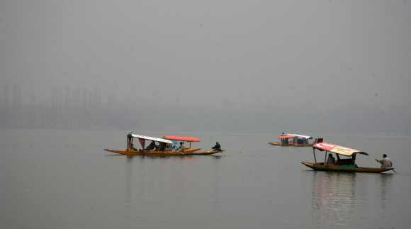 Kashmiri tourists enjoy a shikara ride as fog envelopes the Dal Lake