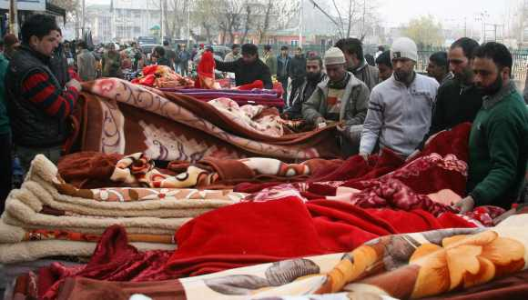 Locals buy blankets at a market in Srinagar