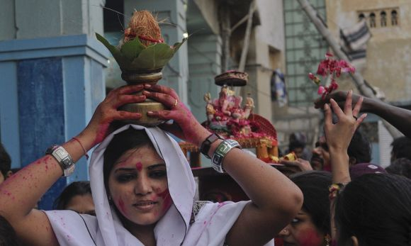 A Hindu woman carries a coconut on her head as an offering for Lord Ganesh during Ganesh Chaturthi festival at the Laxmi Narain Temple in Karachi