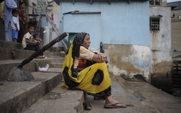 A woman sits alone while waiting for the celebrations on the first day of Ganesh Chaturthi at a temple in Karachi