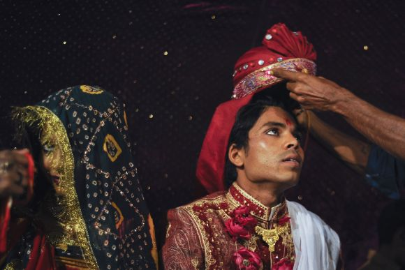 Sanjay wears a turban as he sits beside his wife Jasoda during a mass marriage ceremony in Karachi organised by the Pakistan Hindu Council