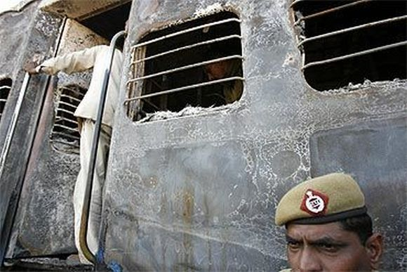 A policeman stands outside a burnt carriage of Samjhauta Express train near Panipat on February 2007 following two bomb blasts