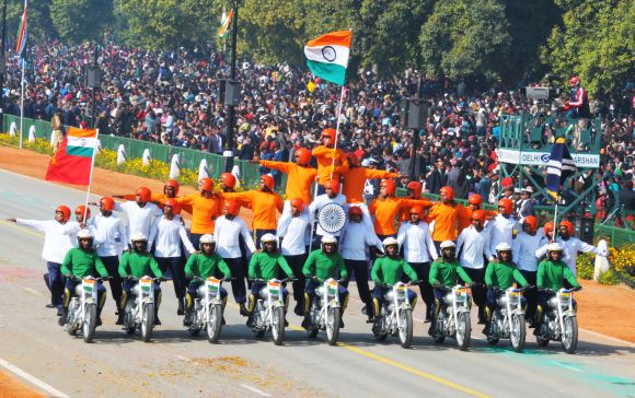 Rajpath comes alive with the dare devil stunts of motorbike riders of Border Security Force, during the 64th Republic Day parade.