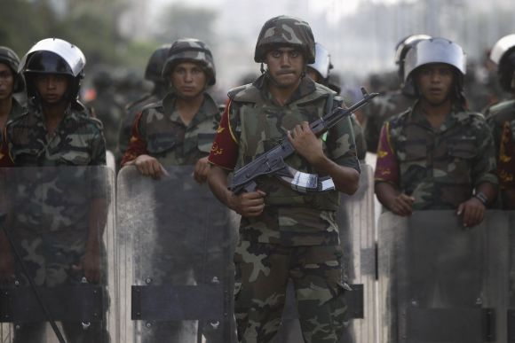 Army soldiers take their positions in front of protesters who are against Morsi, near the Republican Guard headquarters in Cairo