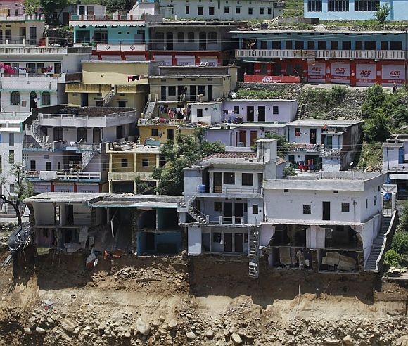Buildings destroyed during floods are seen next to the Alaknanda river in Govindghat