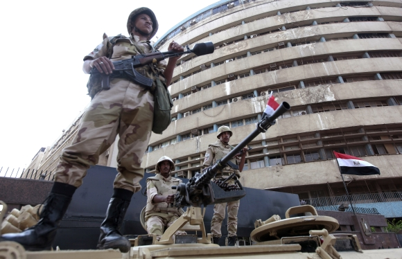Soldiers stand on an armoured personnel carrier positioned outside the state-run television station in Cairo on Saturday