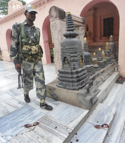 A security personnel walks next to bloody footprints inside the Mahabodhi temple complex