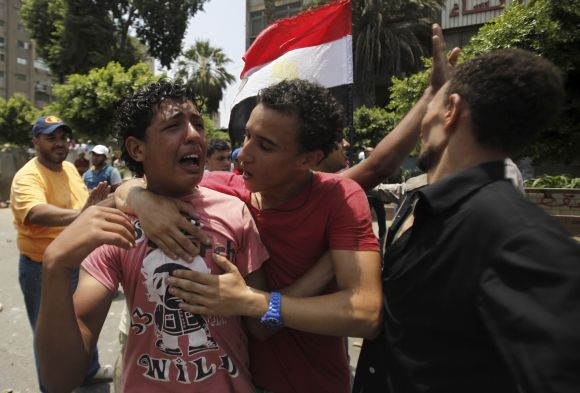 Members of the Muslim Brotherhood react at Republican Guard headquarters in Nasr City.