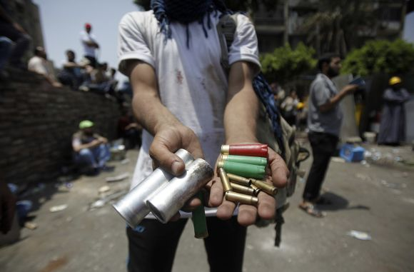 A member of the Muslim Brotherhood displays spent ammunition after clashes with army in front of Republican Guard headquarters