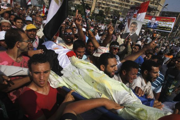 Supporters of Mursi carry the body of a fellow supporter killed in violence outside the Republican Guard headquarters in Cairo