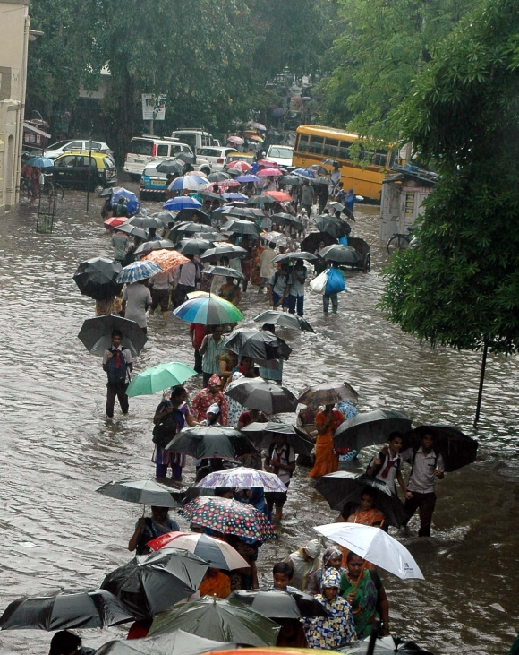 Commuters wades through a water-logged road in Dharavi, Central Mumbai