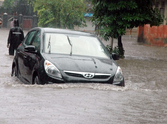 A vehicle makes its way through a flooded street in Mahim, Central Mumbai.