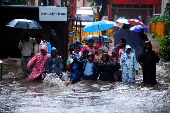 Schoolchildren and their parents struggle at a waterlogged Hindmata Chowk in Central Mumbai
