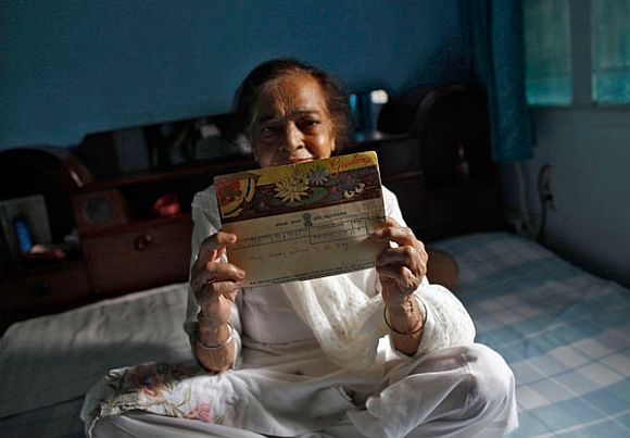 Surjeet Kaur, 77, displays a telegram which was sent by her husband on her birthday in 1955, inside her house in New Delhi