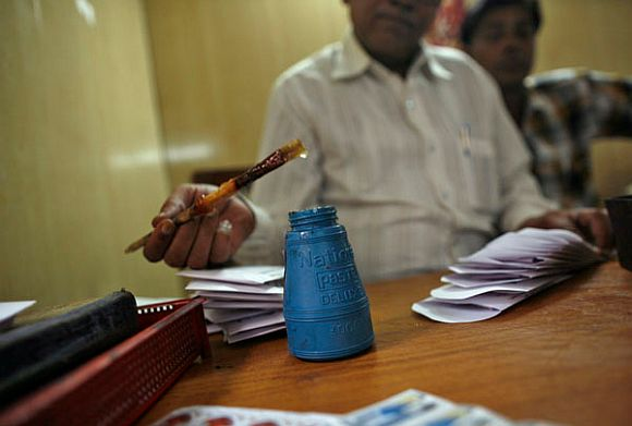 An employee uses glue as he prepares telegrams to be sent at the Central Telegraph Office in New Delhi