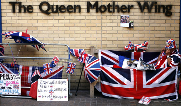 A Royal fan reads the newspaper outside St Mary's Hospital opposite the Lindo Wing