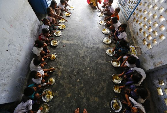 School children eat their free mid-day meal at a school in Bihar's Chapra district