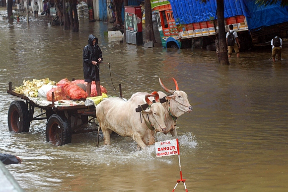 A vegetable vendor trudges through a waterlogged road at Elphinstone Road