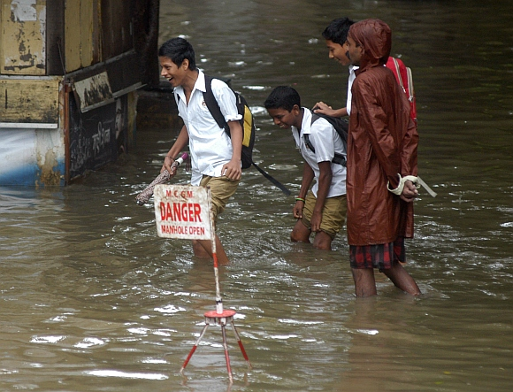 Schoolchildren wade through water at Parel