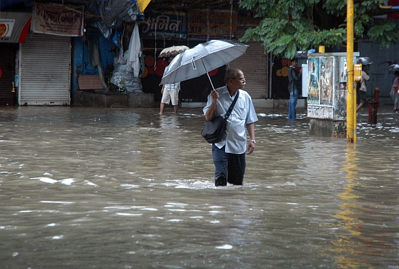 An office-goer makes slow progress as he trudges through a flooded road in Parel