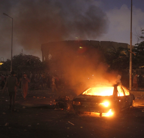 A car that members of the Muslim Brotherhood and supporters of deposed Egyptian President Mohamed Morsi say was burnt by police and plain-clothed people is seen during clashes in Nasr city area, east of Cairo