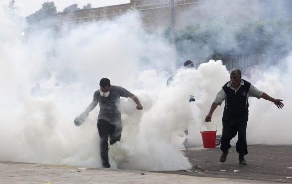 Supporters of Morsi run from tear gas fired at them by police during clashes in Nasr city area