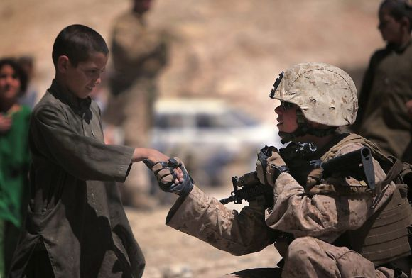 Sgt. Julie Nicholson, Female Engagement Team leader, Marine Headquarters Group, I Marine Expeditionary Force, shakes hands with an Afghan child during a mission in Helmand Province, Afghanistan