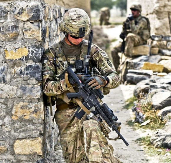 US Army Sgt. Eric Rothenberger checks his sights while pulling security at an alleyway in the village of Kunday