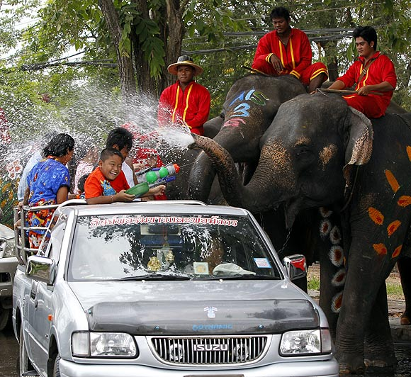Elephants spray water at children in celebration of the Songkran water festival in Thailand's Ayutthaya province