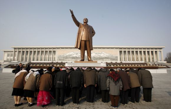 A group of people bow at the base of the giant bronze statue of the state founder and 'Great Leader' Kim-Il Sung in the North Korean capital of Pyongyang
