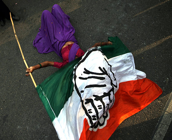 A supporter lies on the ground holding a Congress party flag