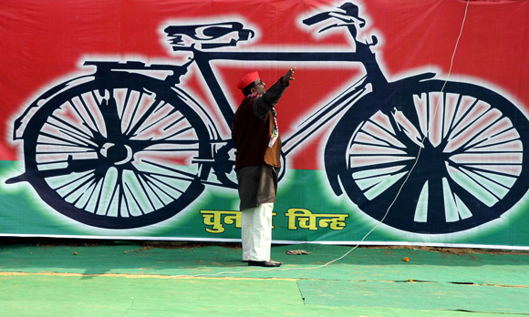 A Samajwadi Party worker gestures in front of a banner with the party's electoral symbol, the bicycle