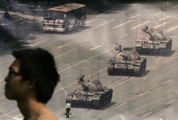A man walks past a banner, printed with a photo of a man standing in front of tanks during the 1989 military crackdown on pro-democracy protesters around Beijing's Tiananmen Square, at Hong Kong's Victoria Park