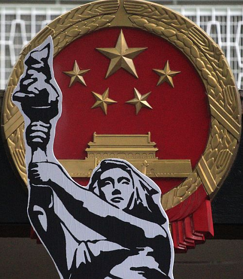 A cut-out of a poster of the Goddess of Democracy is carried by a protester past a Chinese national emblem outside the government headquarters in Hong Kong