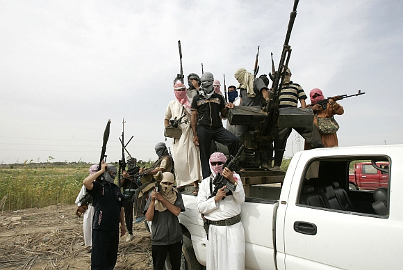Tribal men pose with their weapons as they patrol a road north of Ramadi, 100 km west of Baghdad