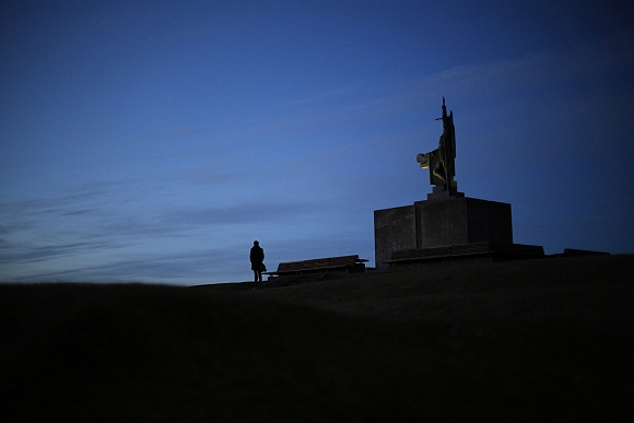 A man stands next to the monument of Ingolfur Arnason, known as Iceland