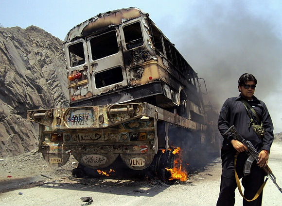 A tribal policeman stands guard near a burning North Atlantic Treaty Organistation supply convoy in Jamrud, Khyber tribal region of Pakistan