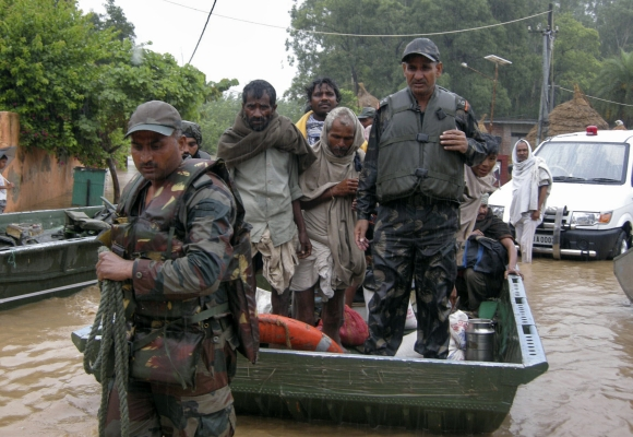 Army soldiers rescue stranded villagers in a boat after floods triggered by heavy rains at Odhri village in Yamunanagar, Haryana