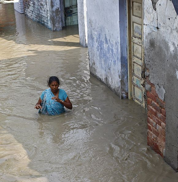 Residents wade through an alley flooded with the rising water level of river Yamuna after heavy monsoon rains in New Delhi on Wednesday