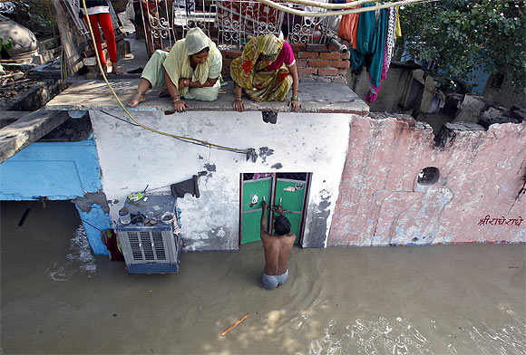 A man unlocks the door of his flooded house as other residents watch after a rise in the water level of river Yamuna in New Delhi