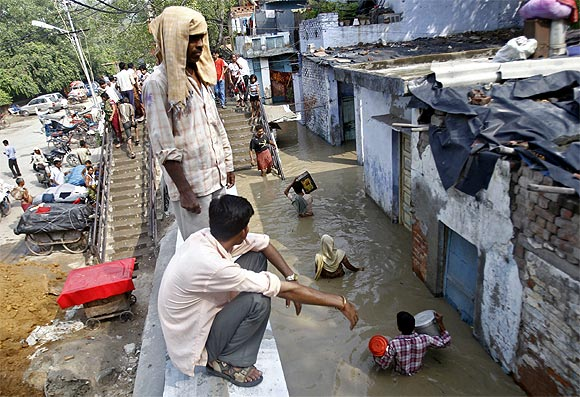 Residents carry their belongings through an alley flooded with the rising water level of river Yamuna