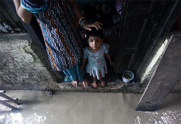 A child watches while standing on the doorstep of her house next to a flooded alley due to rising water level of river Yamuna