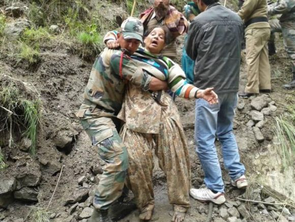 An army personnel rescues an injured person in rain-ravaged Uttarakhand