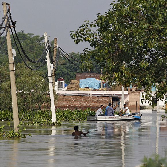 Residents use a boat to secure their belongings from a flooded colony after heavy monsoon rains caused the rise in waters of Yamuna river